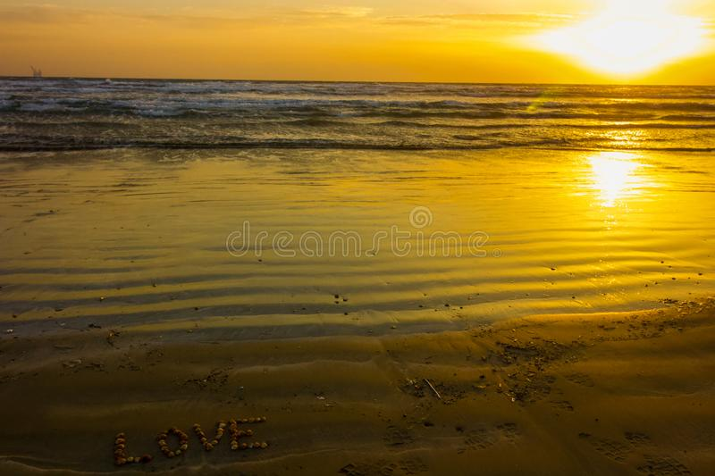 Love beach at sunrise, sandy background with seashells, sun rising over the mediterranean sea stock image