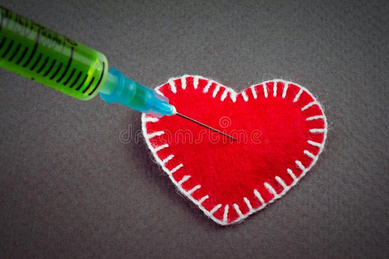Love betrayal concept. In the decorative heart made of red fumirana sewn with a white thread, a syringe with a green poison pierces. love betrayal concept. gray stock images