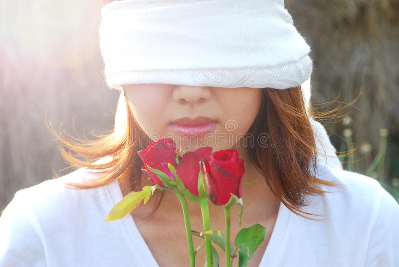 Love is blind. Asian young woman are bind with white scarf on her eyes in the light and flare in sunshine evening. In concept love is blind stock images