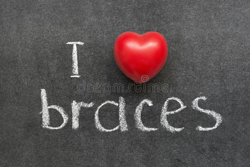 Love braces. I love braces phrase handwritten on chalkboard with red heart symbol stock photography