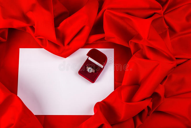 Love card with diamond ring on a red fabric. Love card. red jewel box with diamond ring on white paper and red fabric royalty free stock photos