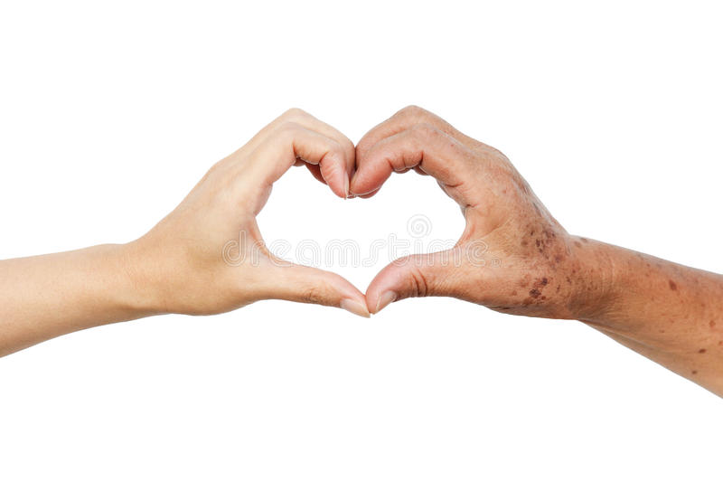 Love and care. Hands of the female elderly and a young woman forming a heart shape together / Love and care elderly people concept royalty free stock image
