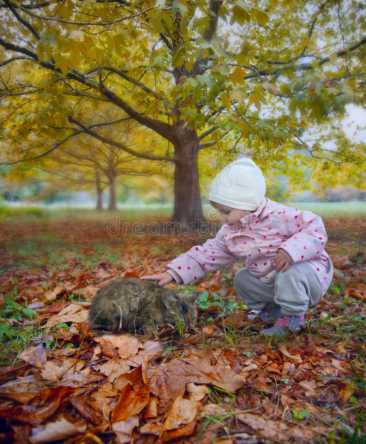 Love cat. Little girl with homeless cat in autumn park
