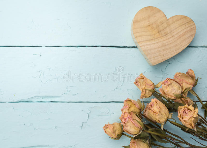 Love celebration background of dried peach roses and wooden carved heart isolated on rustic painted blue table stock images
