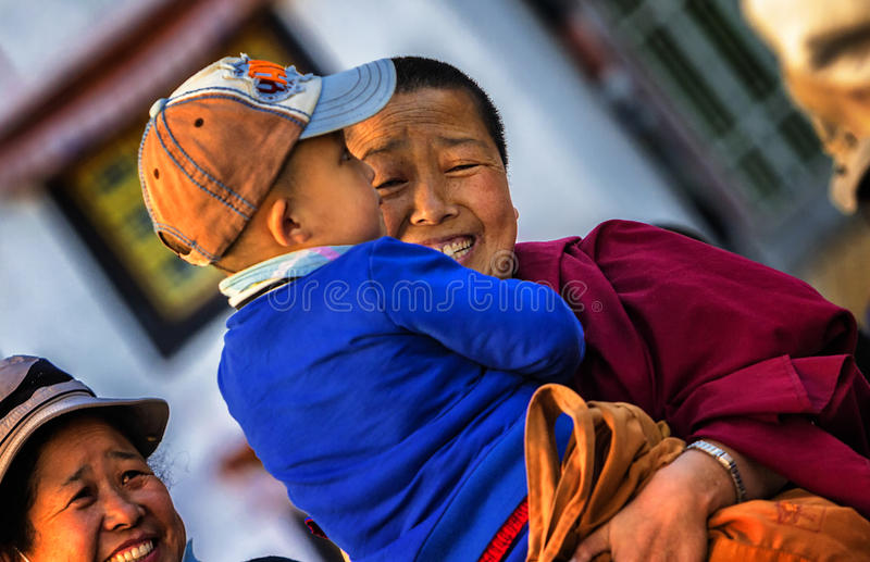 Love the child`s nun. October 2, 2016 in Tibet, China, a nun holding a friend`s child happy smile, his face full of love stock images