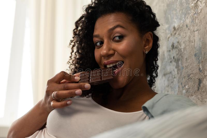 Pretty woman eating a chocolate bar and smiling. royalty free stock images