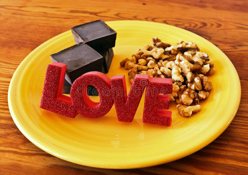 Love Chocolate Walnuts. On a yellow plate and a butcherblock royalty free stock images