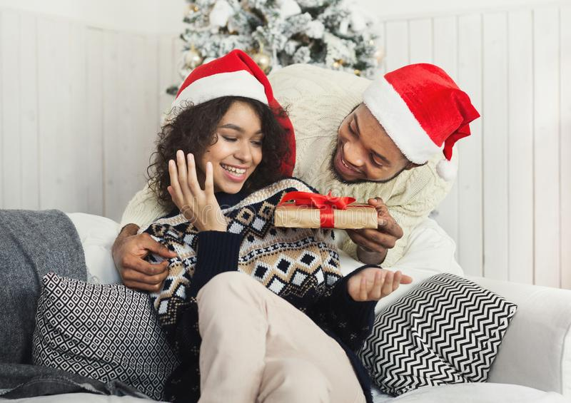 Handsome man surprising girl with Christmas present royalty free stock images