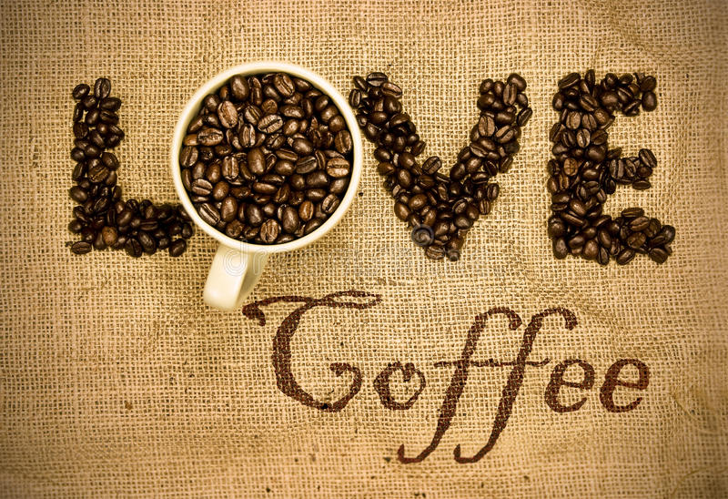 Love coffee. Coffee beans and mug used to spell love on hessian sack stock images