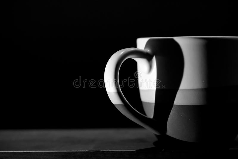 Love Coffee. A monochrome image, there is a symbol of love on a coffee mug that arise from the handle and shadow stock photos