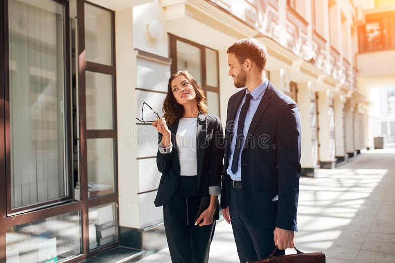 Love between colleagues, man in stylish suit with briefcase seeing colleague off stock images
