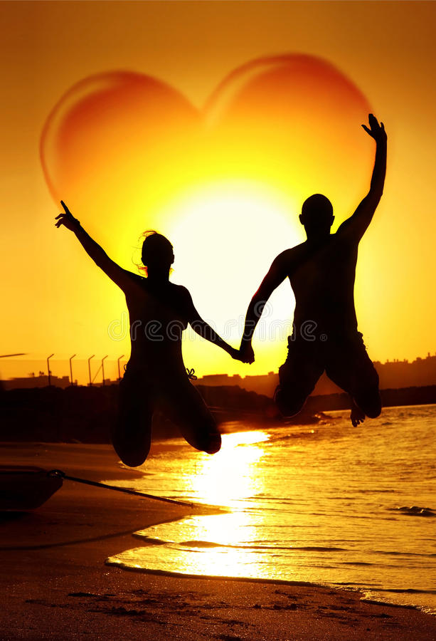 Love concept. Happy young couple jumping, holding hands with heart shape in the sky, symbol of happiness, family playing outdoor, sunset on the beach, fun royalty free stock images
