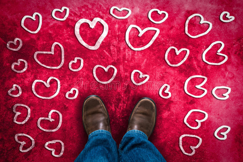 Love concept with Brown leather shoes. And hand drawn hearts symbol. red pink grunge background stock photo