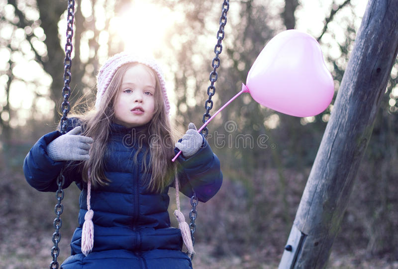 Love concept: child on a swing holding a heart-shaped baloon. stock photos