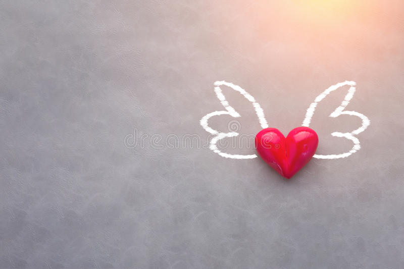 Love concept with red heart object with wings drawing on grey ba. Ckground with free copy space for your text stock photo