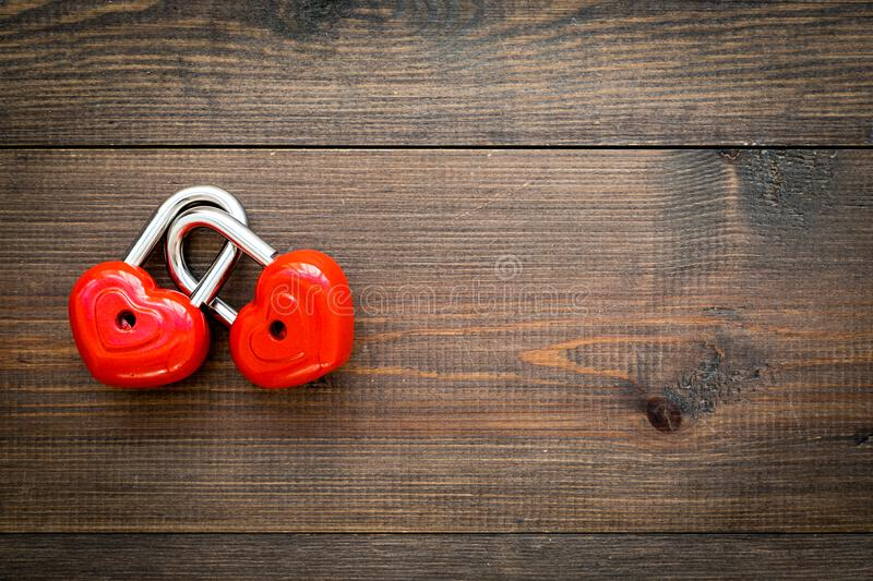 Love concept. Valentine`s day symbol. Locks in shape of heart o dark wooden background top view copy space stock photos
