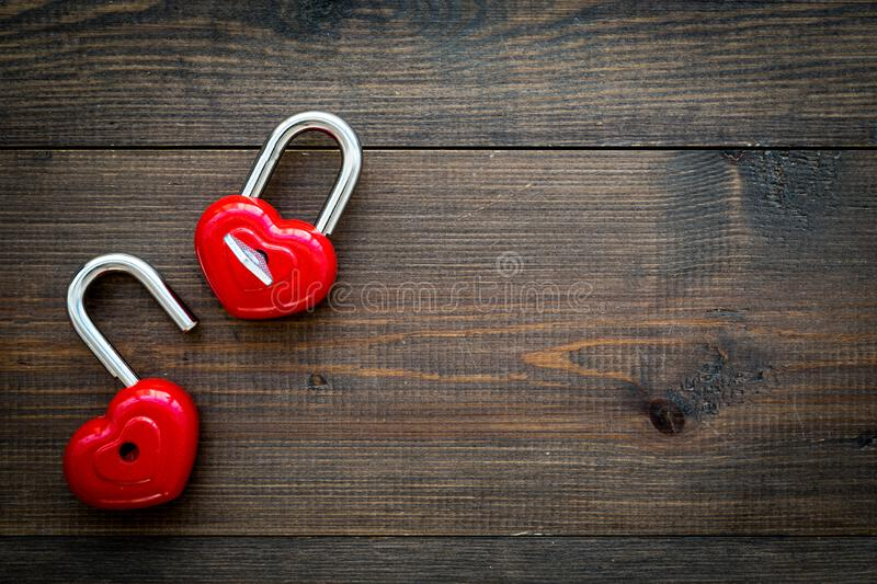Love concept. Valentine`s day symbol. Locks in shape of heart o dark wooden background top view copy space stock image
