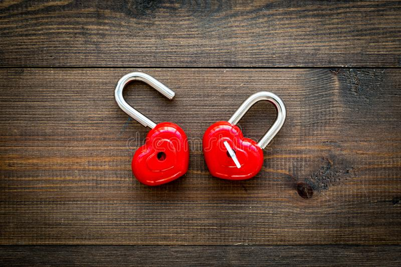 Love concept. Valentine`s day symbol. Locks in shape of heart o dark wooden background top view copy space royalty free stock images