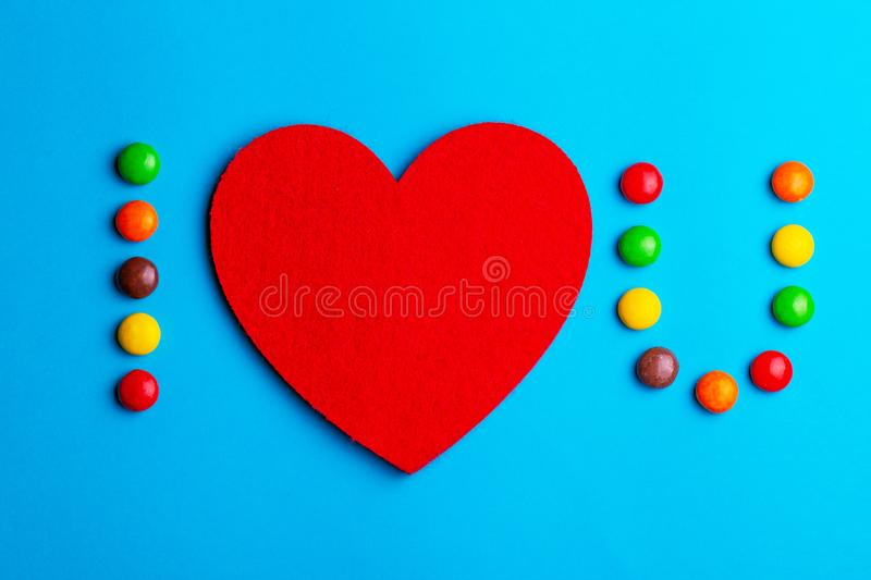 Love confession with help of glazed candies and felt heart royalty free stock photography