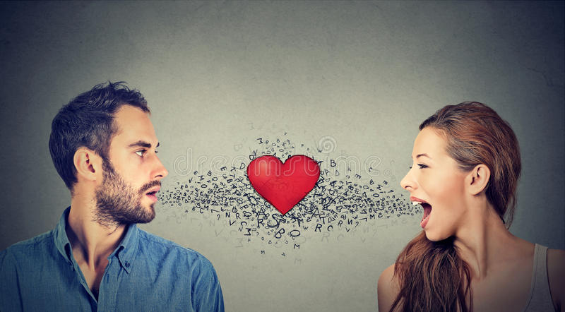 Love connection. Man woman talking to each other red heart in-between royalty free stock photo