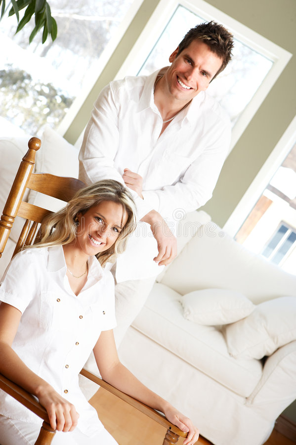 Love couple. Young love couple smiling in the comfortable apartment stock images