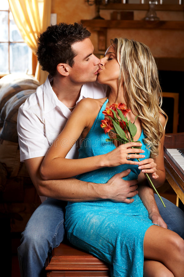 Love couple. Young love couple kissing in the comfortable apartment royalty free stock image