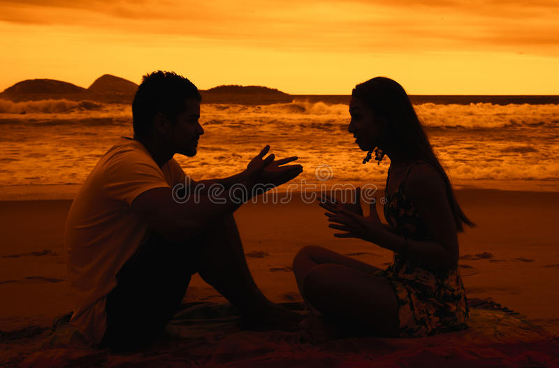 Love couple with relationship difficulties at beach at sunset stock photo