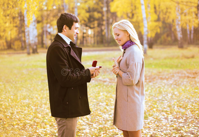 Love, couple, relationship and engagement concept - couple. Love, couple, relationship and engagement concept - men proposing to a women in the autumn park royalty free stock photography
