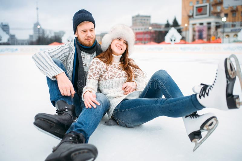 Love couple in skates sitting on ice, skating rink. Young love couple in skates sitting on ice, skating rink. Winter ice-skating on open air, active leisure stock photography