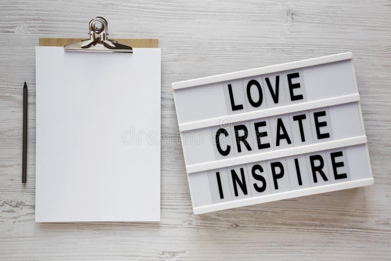 'Love create inspire' Wörter auf einem Leuchtkasten, Zwischenablage mit weißem Blatt Papier auf weißer Holzoberfläche, obere Ansi lizenzfreie stockfotos