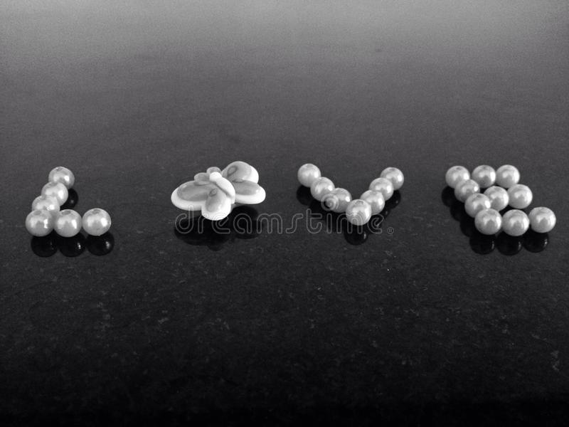Love. Creative creation pearls butterfly word royalty free stock photo
