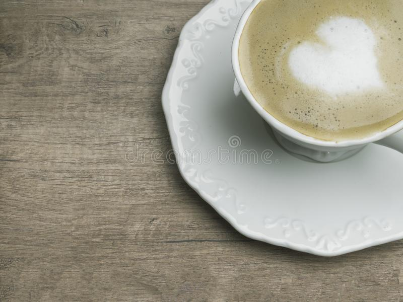 Love cup , heart drawing on latte art coffee. Love cup , heart shape drawing on latte art coffee white coffee with on wood table royalty free stock images