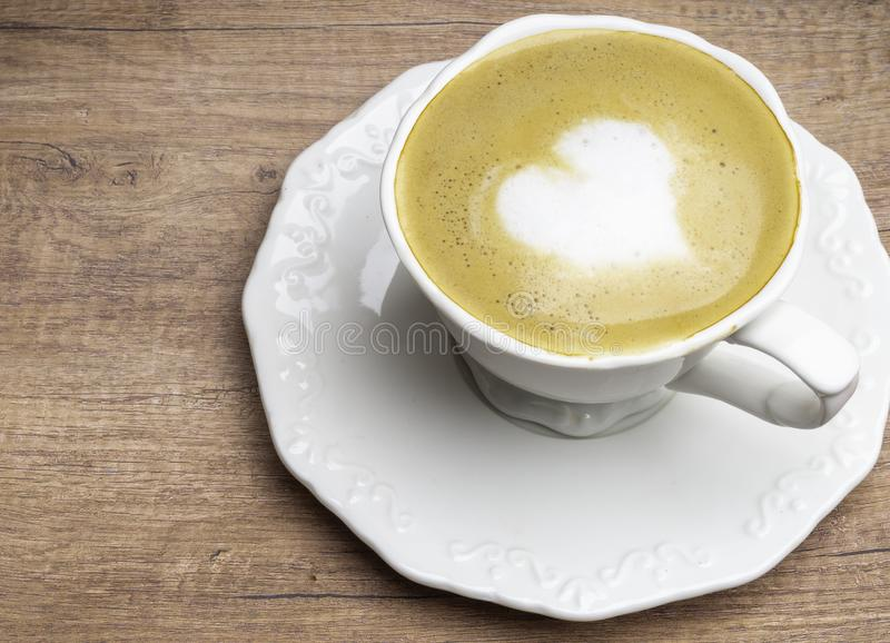 Love cup , heart drawing on latte art coffee. Love cup , heart shape drawing on latte art coffee white coffee with on wood table royalty free stock photography
