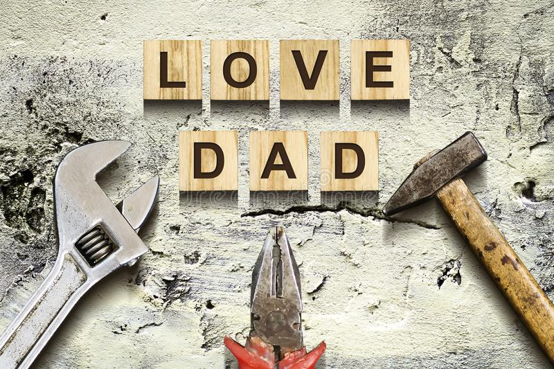 Love Dad inscription on wooden cubes with working tools on an old vintage concrete wall. Happy Father`s Day Concept. Greetings an royalty free stock image