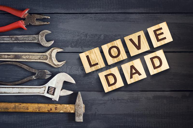 Love Dad inscription on wooden cubes with working tools on a wooden background.Happy fathers day concept. Greetings and gifts. stock image