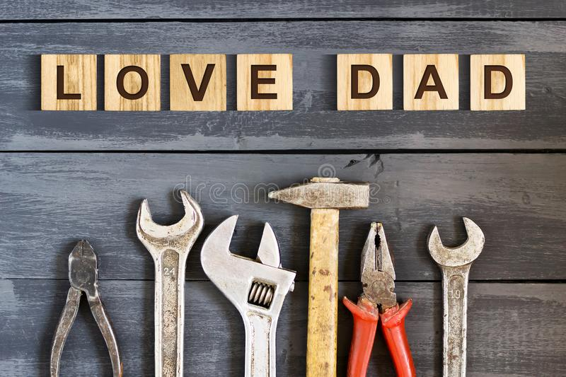 Love Dad inscription on wooden cubes with working tools on a wooden background.Happy fathers day concept. Greetings and royalty free stock photos