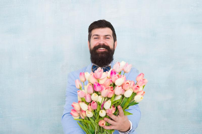 Love date with flowers. Happy Birthday. bride groom at wedding party. bearded man in bow tie with tulip flowers. spring. Bouquet. 8 of march. womens day. Formal stock photography