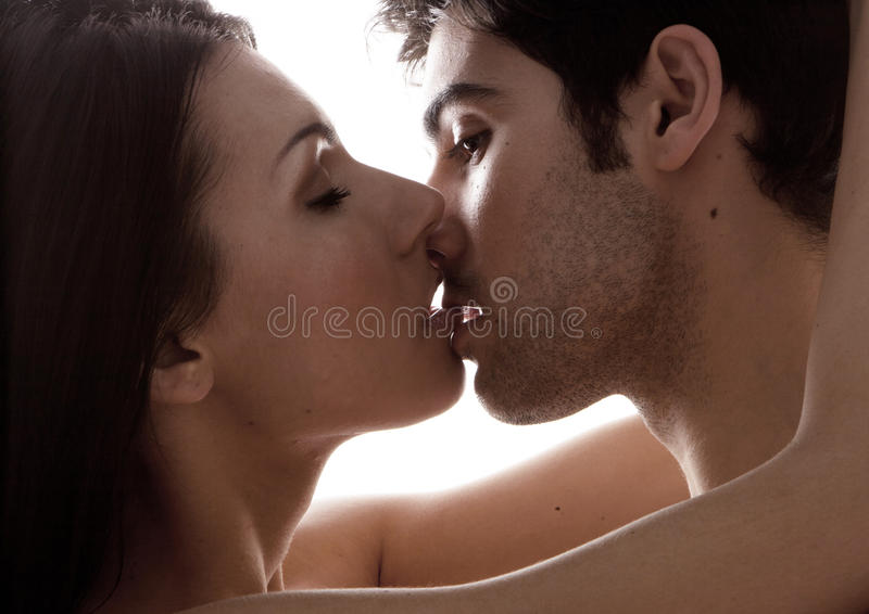 Love And Desire. A closeup facial portrait of a young couple kissing, backlit stock image