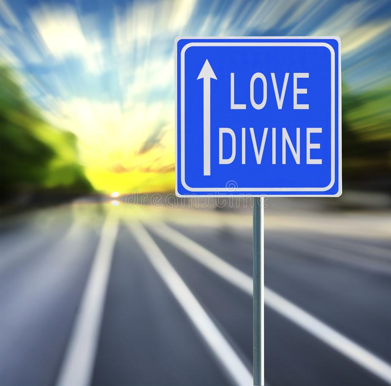 Love Divine Road Sign on a Speedy Background with Sunset. Love divine motivational phrase on blue road sign with arrow and blurred speedy background in sunset stock image