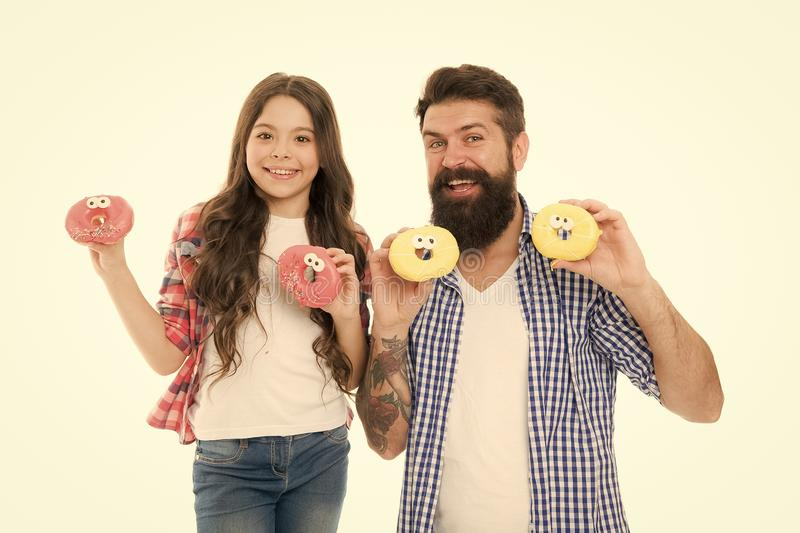 We love donuts. Fathers day present. Perfect for dads with sweet tooth. Girl child and dad hold colorful glazed donuts. Sweets and treats concept. Daughter and stock photography