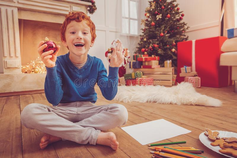 Joyful boy being excited about drawing Christmas decorations stock images