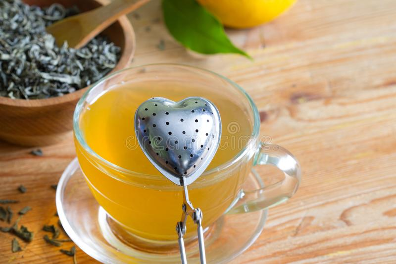 Love drinking tea with infuser heart valentines abstract concept on wooden background. Closeup royalty free stock photography