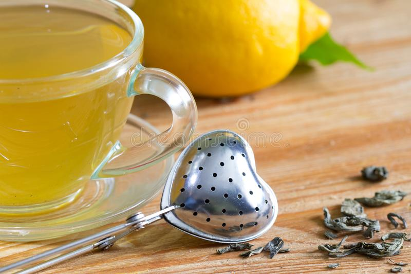 Love drinking tea with infuser heart valentines abstract concept on wooden background. Closeup stock image
