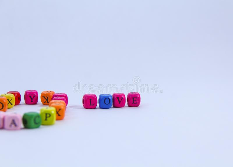 Love alphabet written on colourful wooden block with white background stock photos