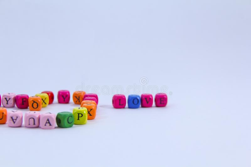 Love alphabet written on colourful wooden block with white background royalty free stock photo