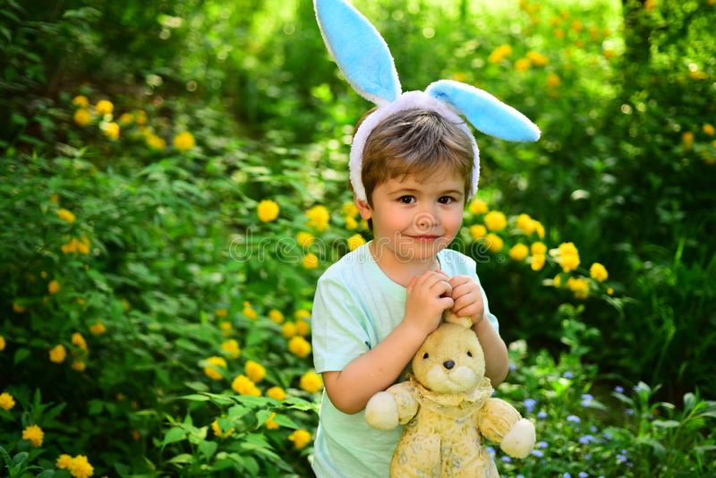 Love easter. Family holiday. Egg hunt on spring holiday. Happy easter. Childhood. Little boy child in green forest. Rabbit kid with bunny ears. Hare toy stock photos