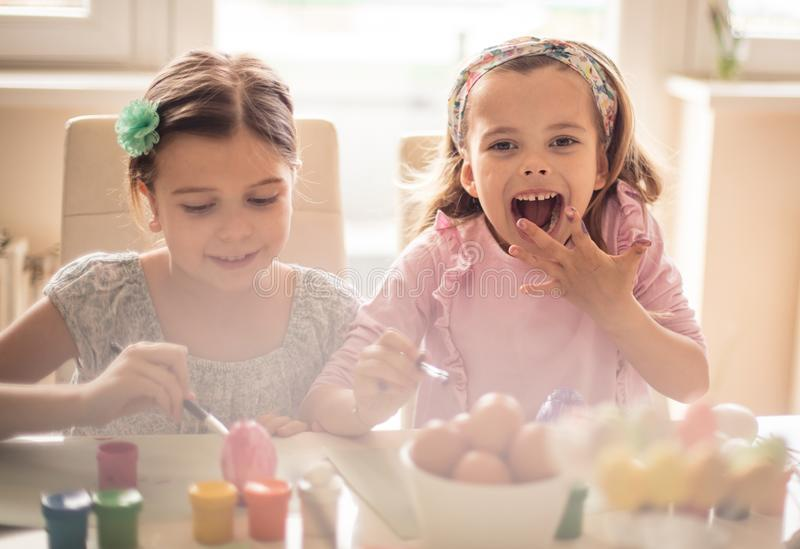 We love Easter. Little girls coloring Easter egg royalty free stock images