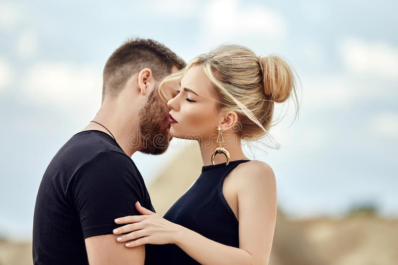 In love Eastern couple in mountains of Cappadocia hugs and kisses. Love and emotions loving couple vacationing in Turkey. Closeup. Portrait men and woman royalty free stock images