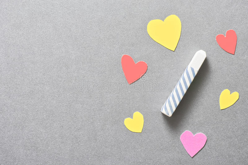 Love education. Colorful paper hearts surrounding a piece of chalk for your concepts about love knowledge, education and information - copy space to the left royalty free stock images