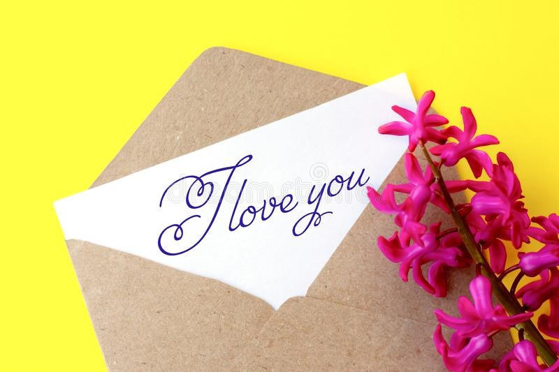 Love envelope and letter with written words I love you with pink hyacinth flowers. On bright yellow background stock photography